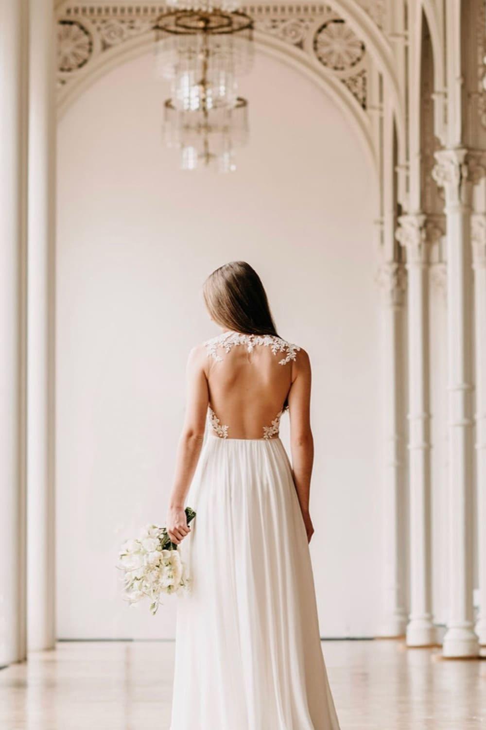 Rückansicht einer Braut mit Spitzen-Kleid und rotem Brautstrauß