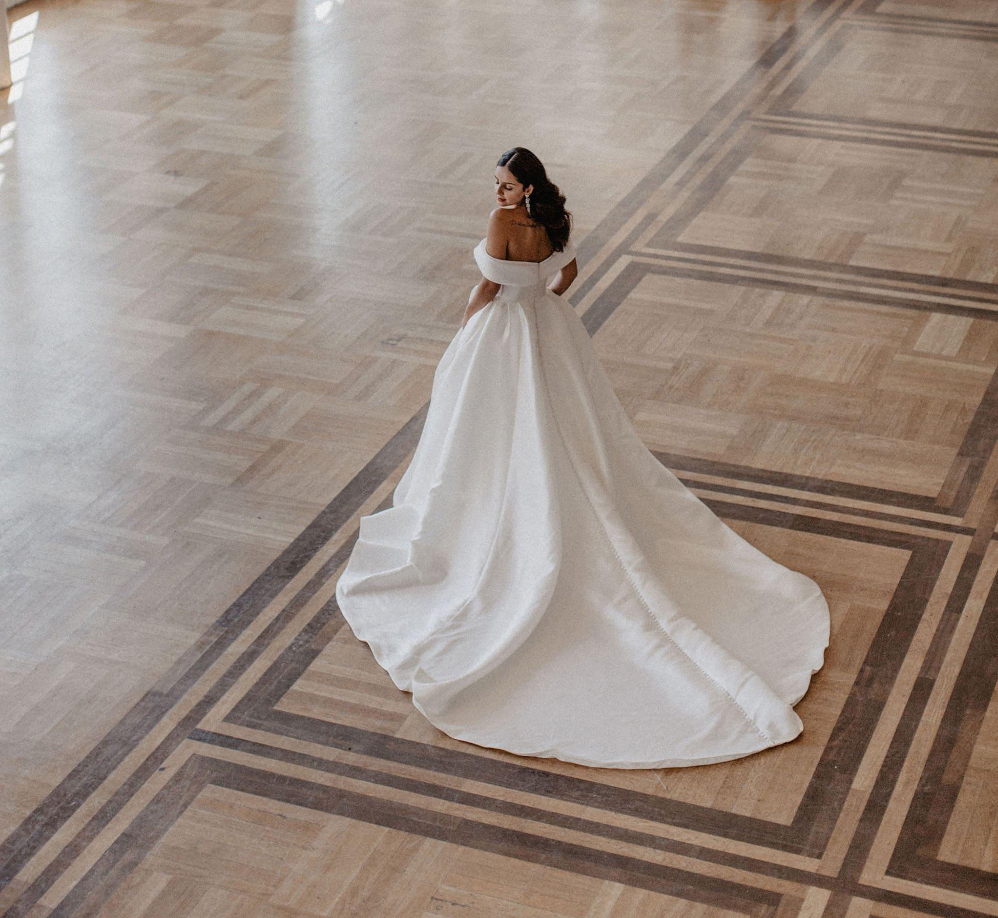 Braut mit weißem Kleid in Ballsaal mit Holzboden