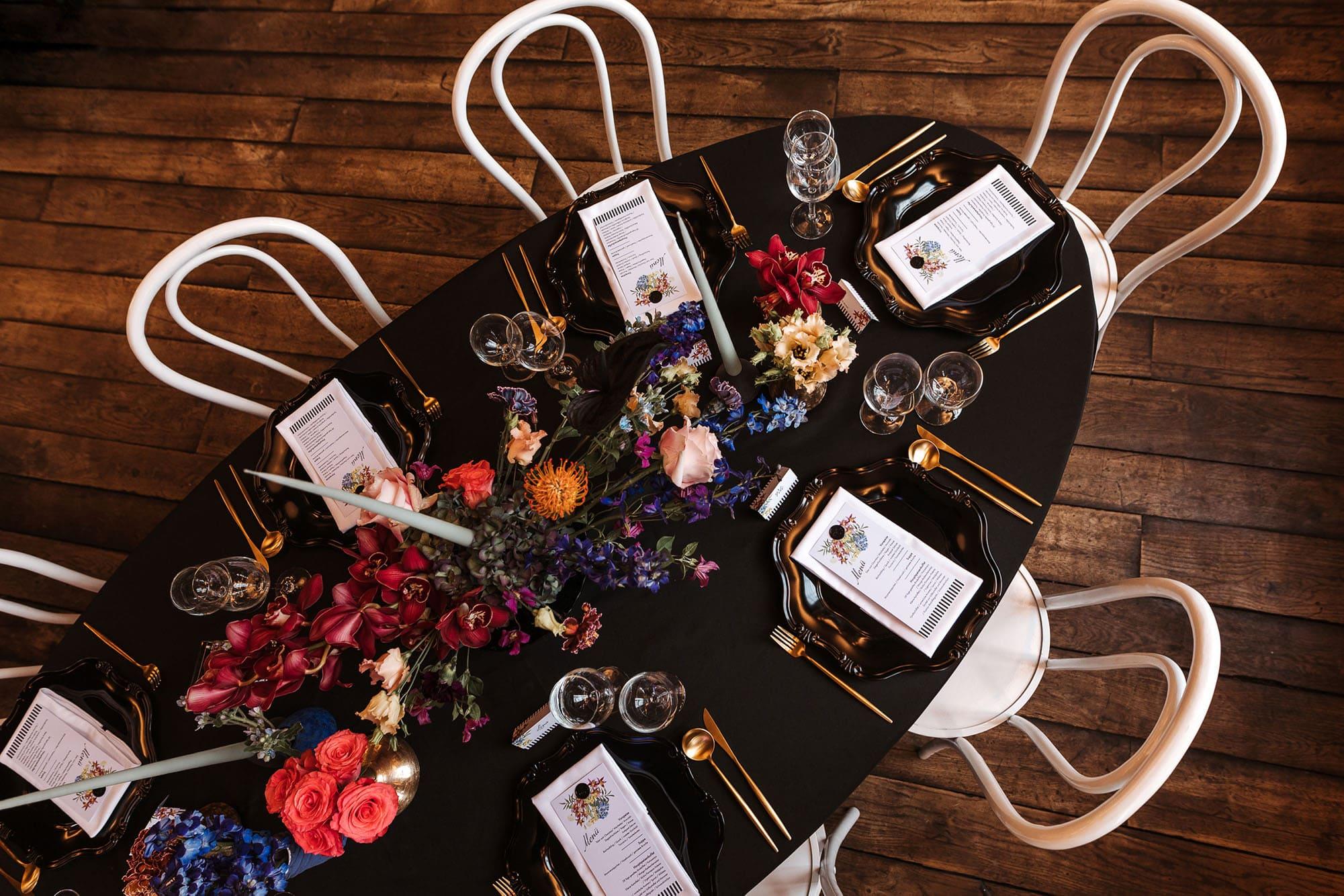 Dekorier ter schwarzer Tisch mit weißen Stühlen und Deko in schwarz und gold