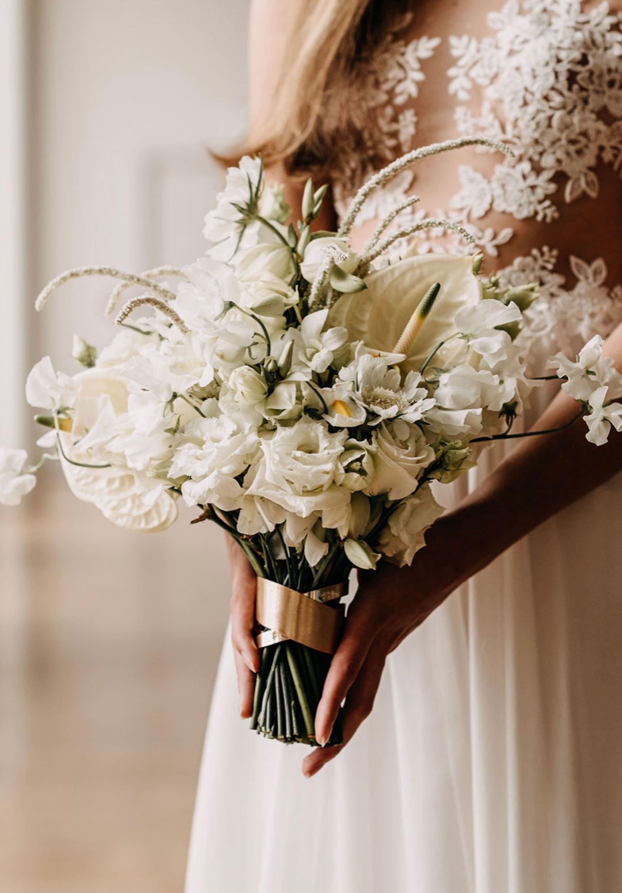 Brautstrauß aus Flamingoblumen und Rosen in Weiß, Braut im Hintergrund