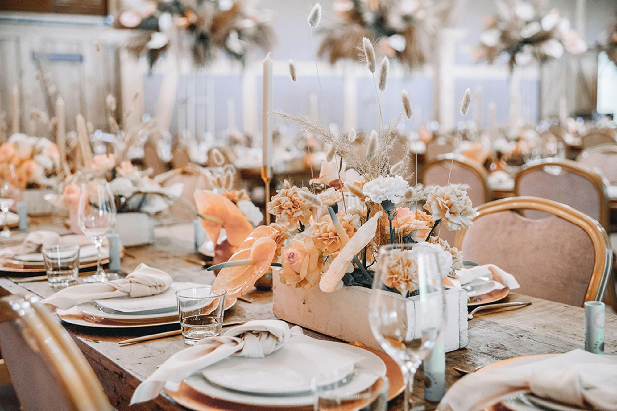 Gedeckte Festtafel mit Blumenschmuck in Apricot und Cremefarben.