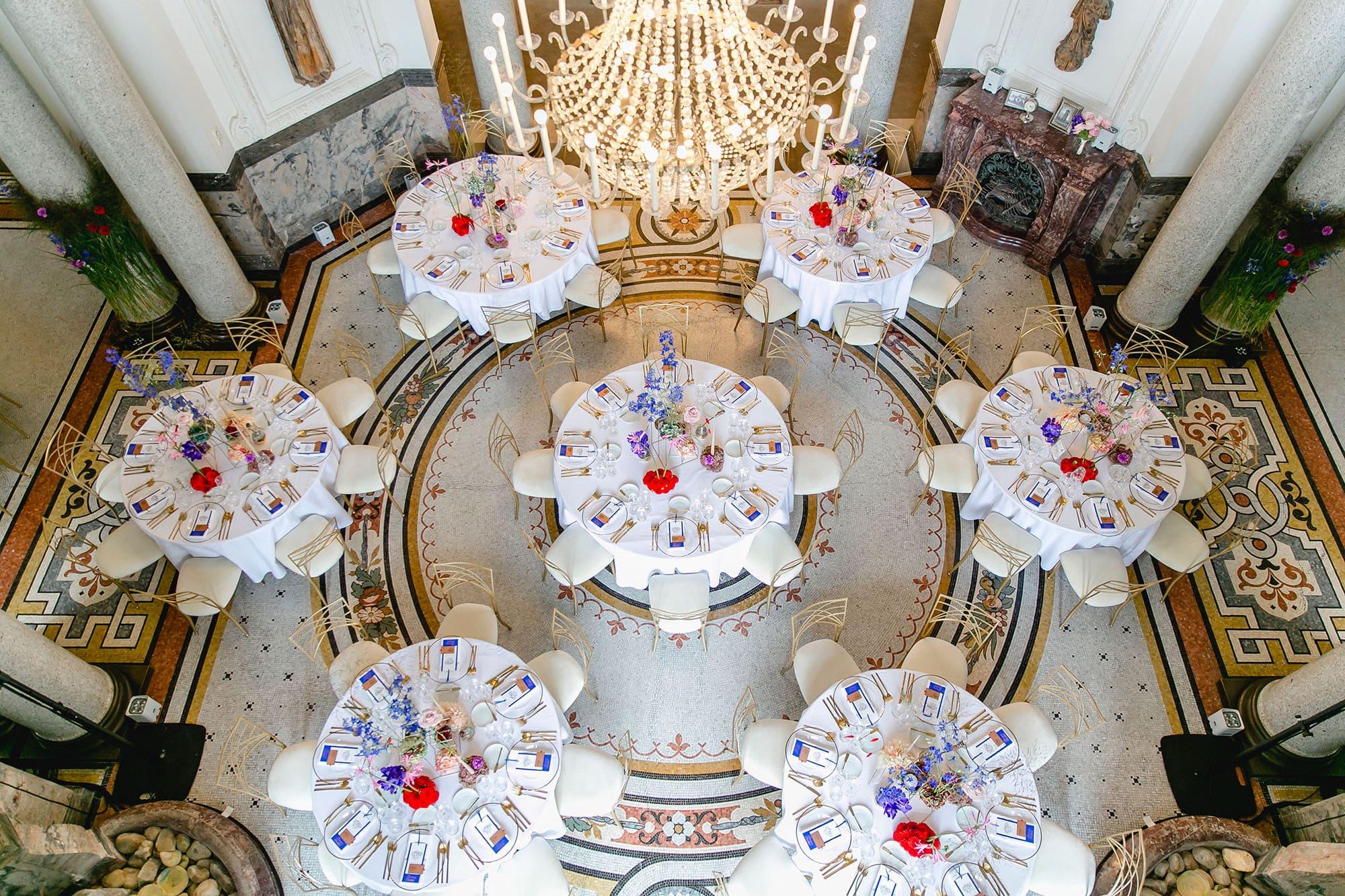 Runde Tische in einem Saal mit weißer Tischdecke und gliehenen Stühlen