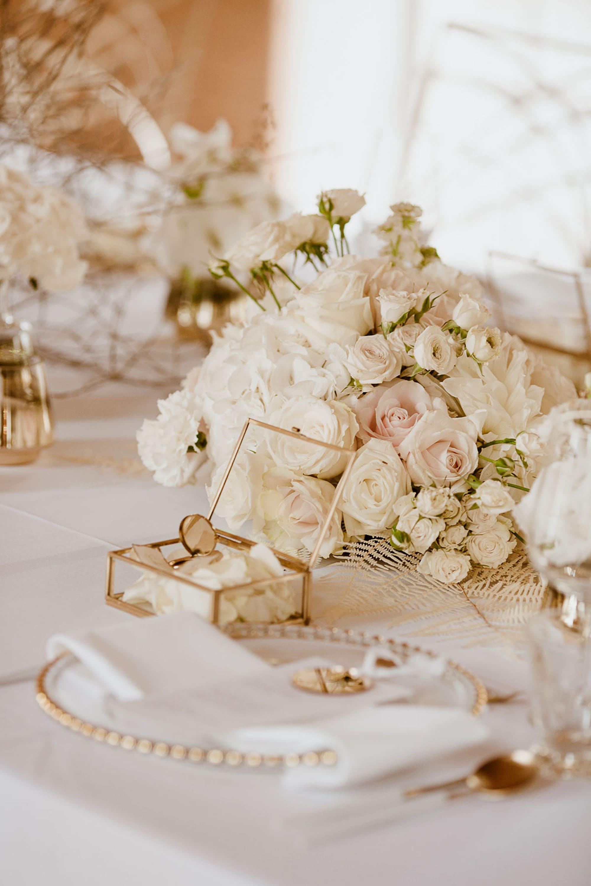 Tischgedeck mit weißen Rosen, Teller mit Goldrand und goldener Schatulle aus Glas