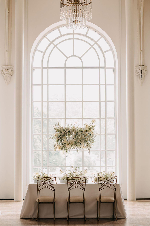 Tisch mit drei Stühlen vor großem Fenster mit weißer Blumen-Deko