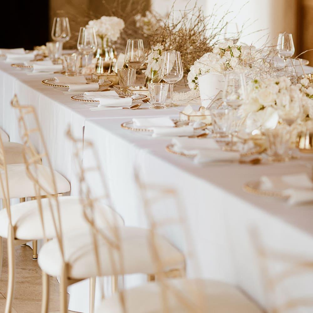 Gedeckte Tafel mit weißer Tischdecke, goldenen Stühlen und Dekoration und gebundenen Zweigen
