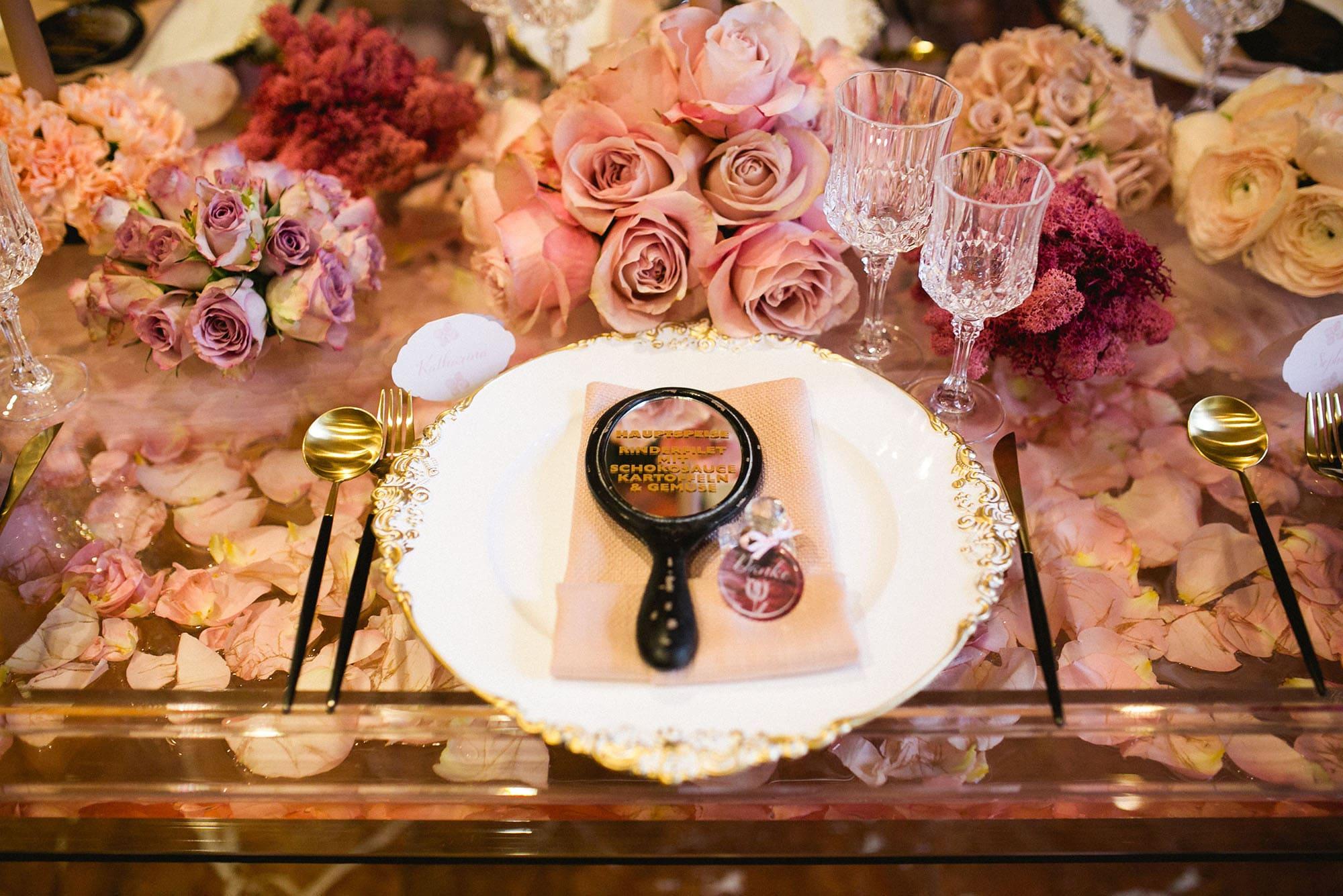 Teller mit Besteck und Gläsern dekoriert mit Rosen und Handspiegel