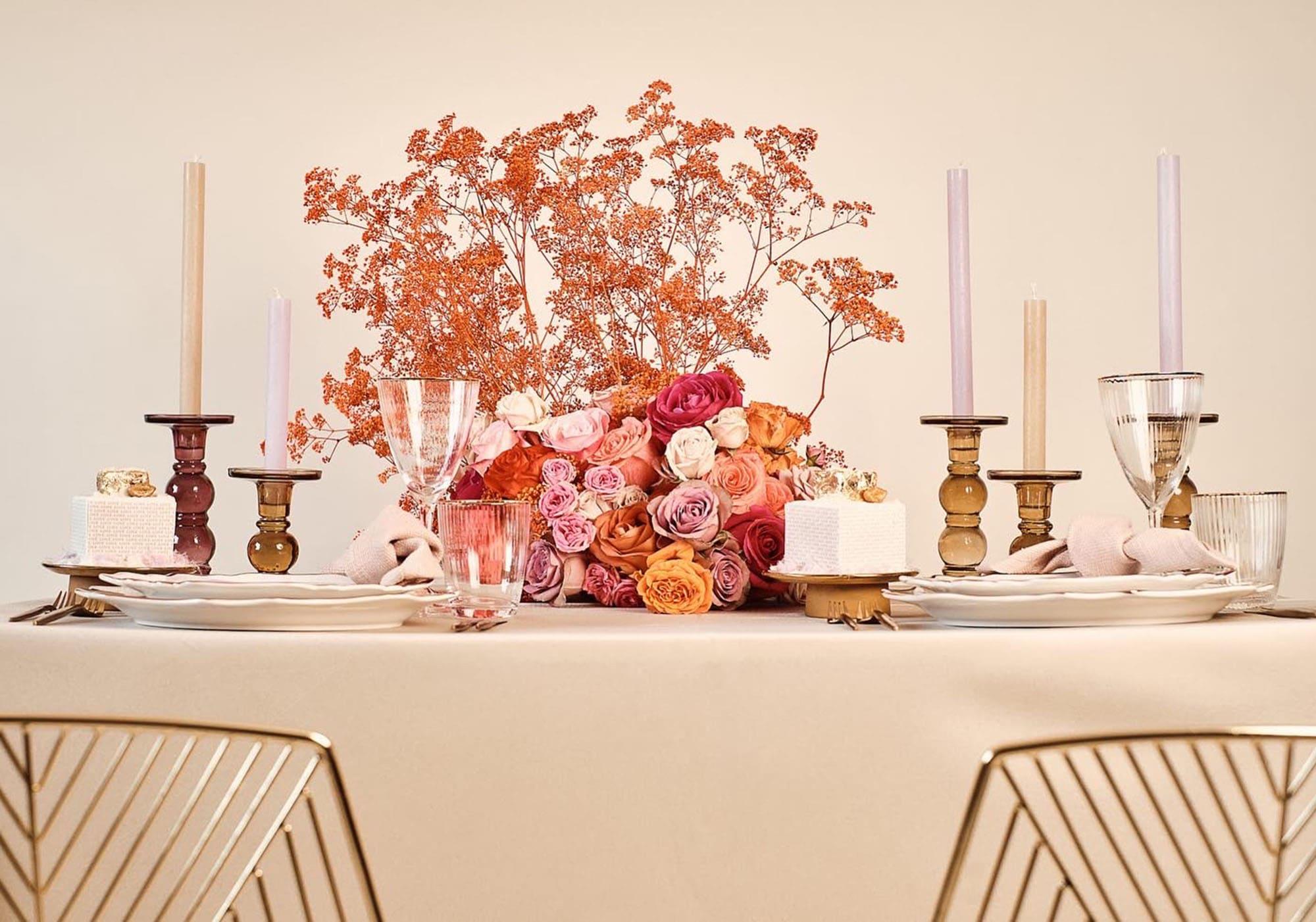 Tischdeko mit Kerzen und Rosenstrauß in Gold- und Rottönen